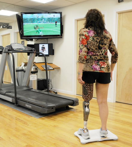 An individual with limb loss using the WiiFit to help improve her gait.
